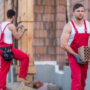 Bauhelfer trägt Ziegelstein auf der Baustelle
