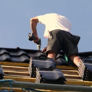 Dachdecker bei der Montage von Dachziegeln
